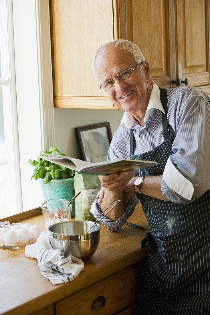 Älterer Mann beim lesen im Rezeptbuch