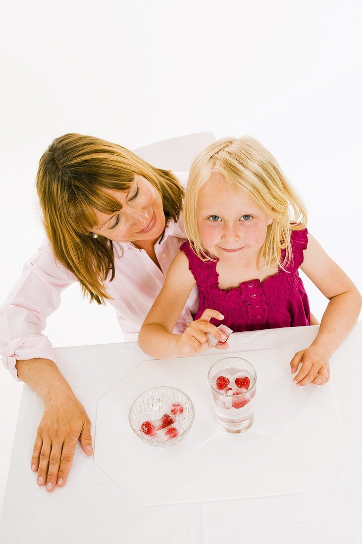 Mother and daughter, daughter holding a raspberry ice cube