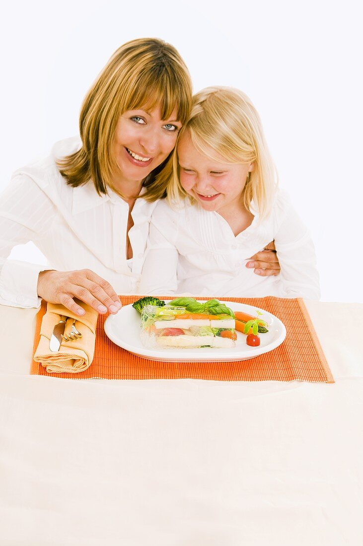 Mother & daughter sitting at table in front of vegetable terrine