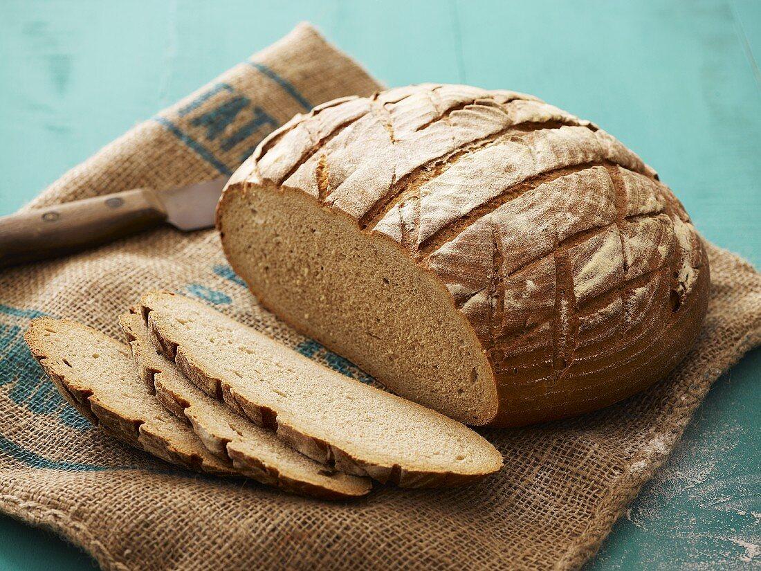 Loaf of bread, partly sliced, on jute sack