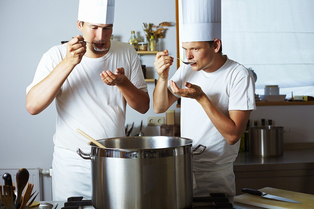 Two chefs tasting soup out of pan