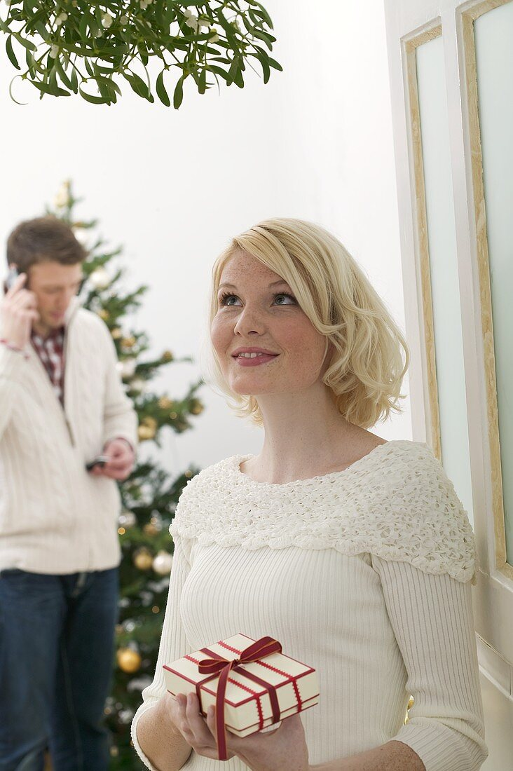 Woman with gift under mistletoe, man in background