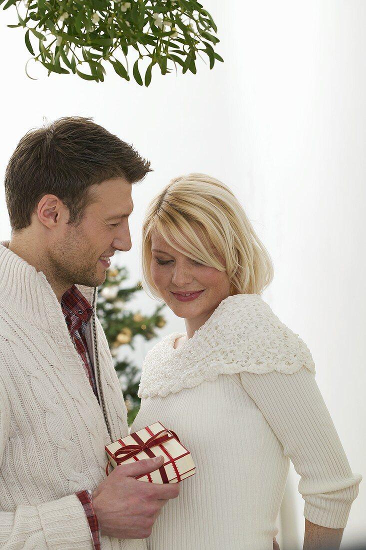 Man giving woman Christmas gift under mistletoe