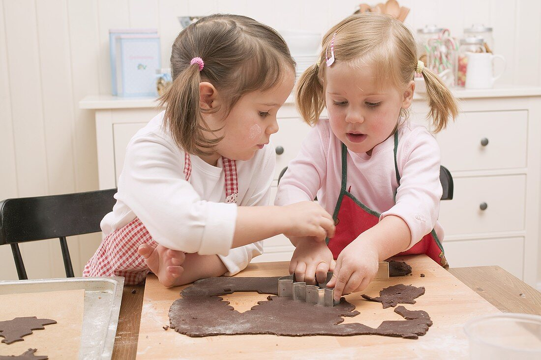 Two small girls cutting out chocolate biscuits