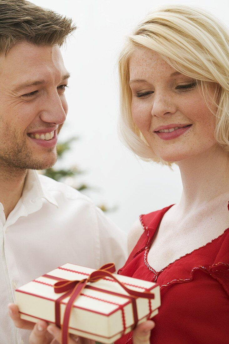 Man giving Christmas gift to woman