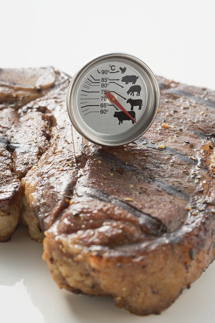 Grilled T-bone steak with meat thermometer