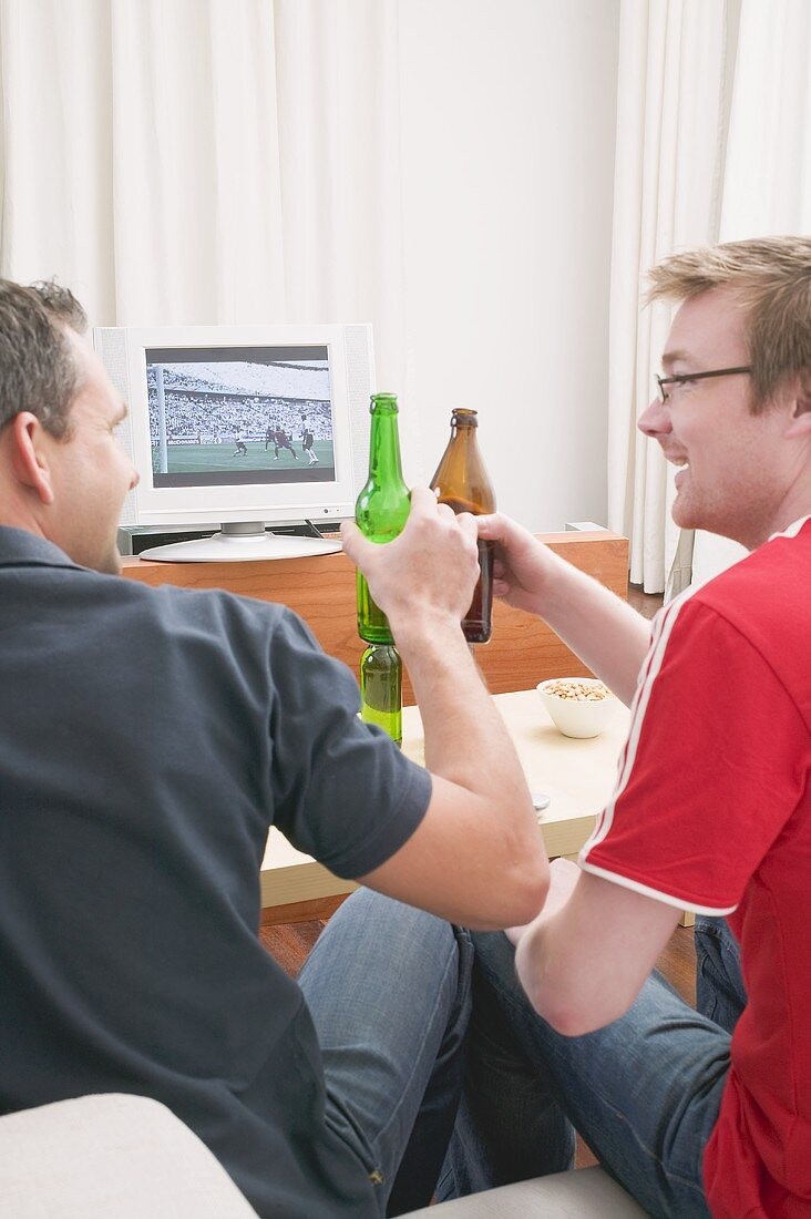 Two football fans clinking bottles of beer while watching TV