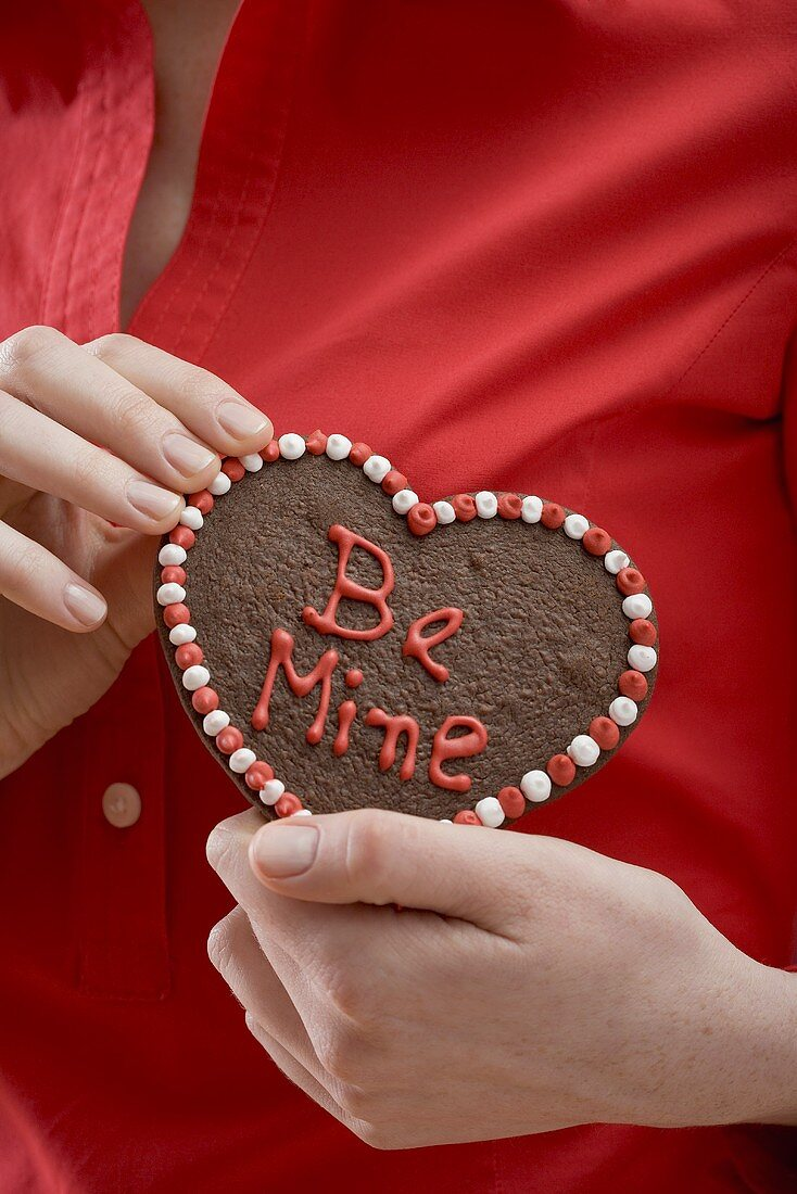 Woman holding chocolate heart with the words Be Mine
