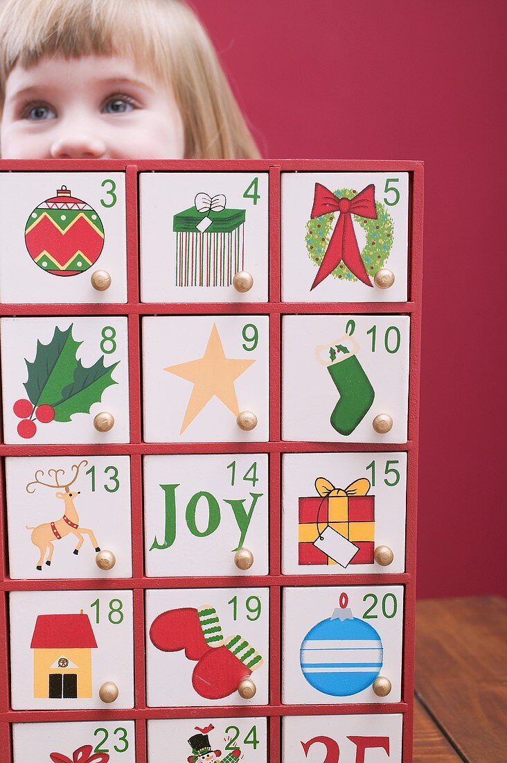 Small girl behind Advent calendar