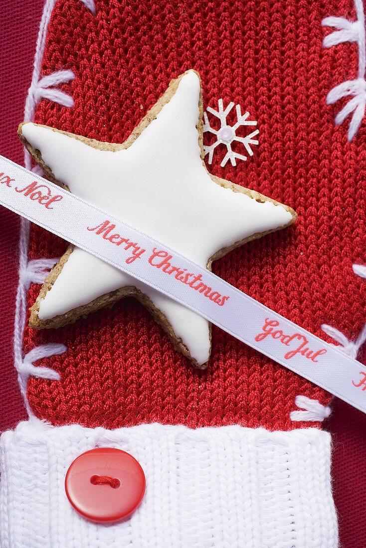 Cinnamon star and Christmas ribbon on woollen mitten