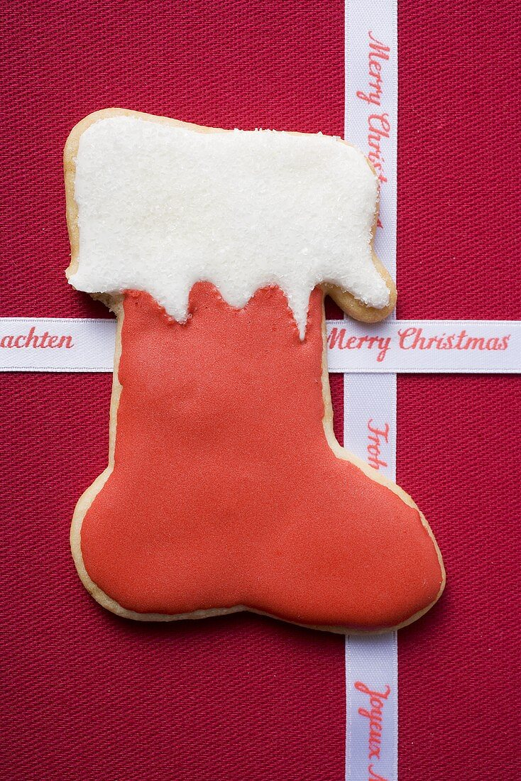 Boot biscuit and Christmas ribbon on red fabric