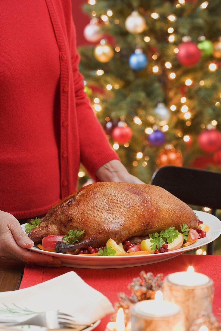 Woman serving roast duck (Christmas)