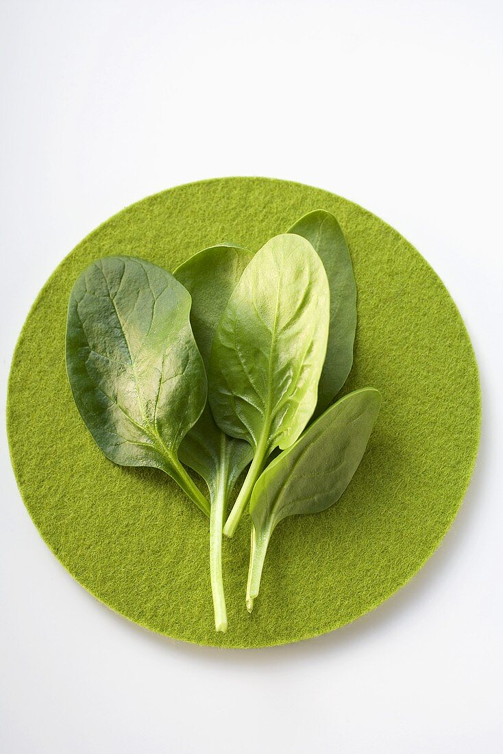 Spinach leaves on green felt circle
