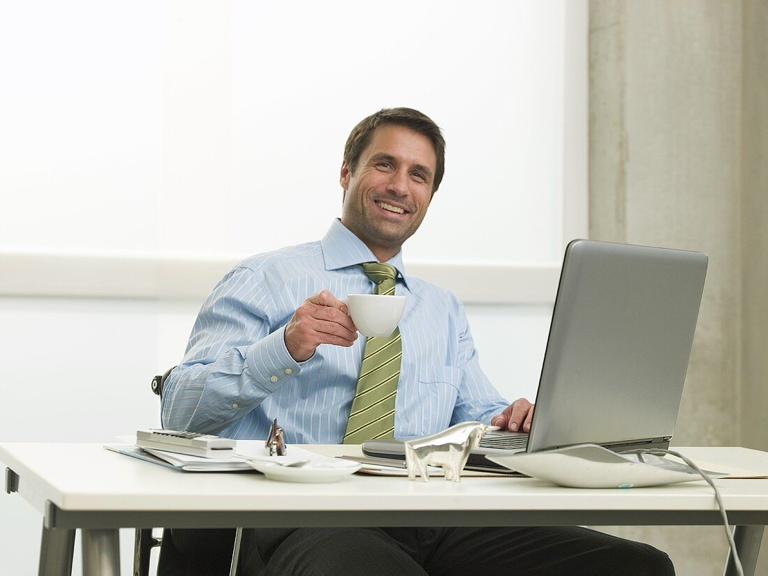 Man drinking coffee sitting at his desk