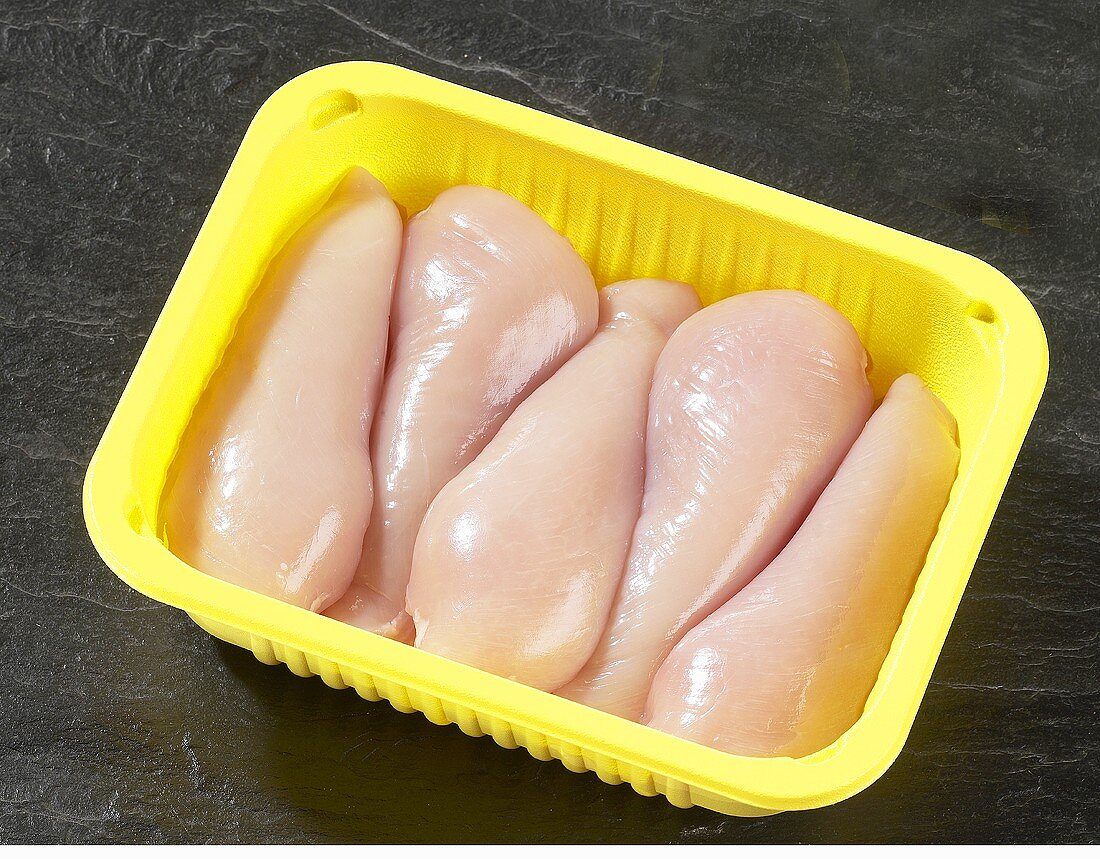 Fresh chicken breast fillets in plastic container