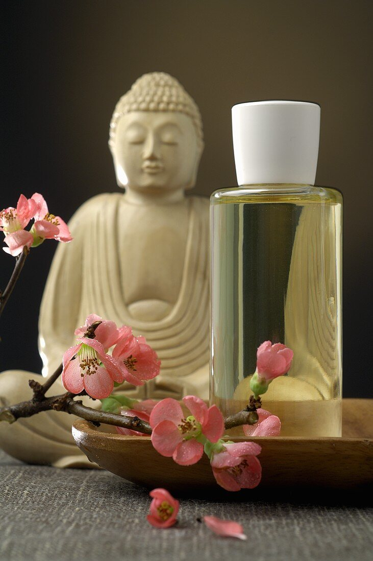 Buddha figure, scented oil and spray of cherry blossom