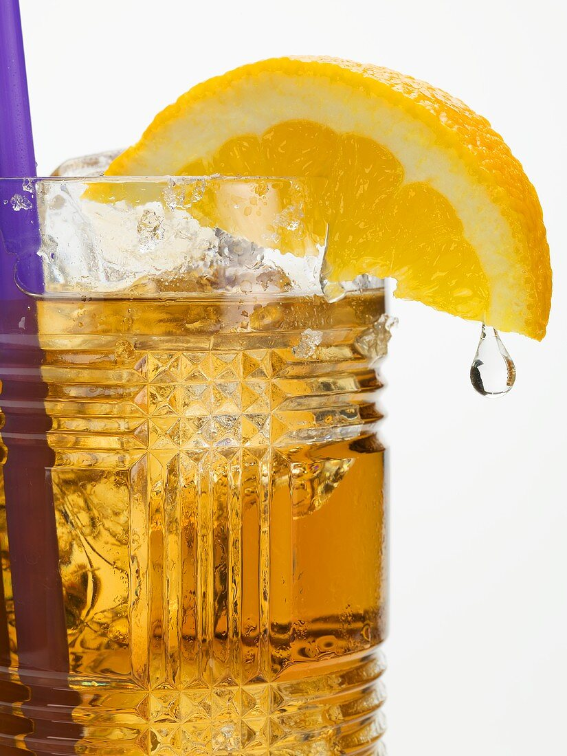 Rum drink with ice cubes and orange wedge with drip