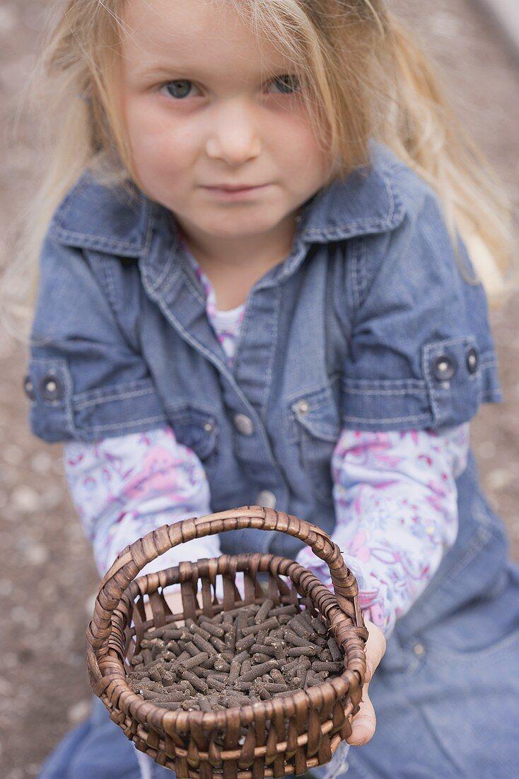 Little girl holding basket of pelleted manure