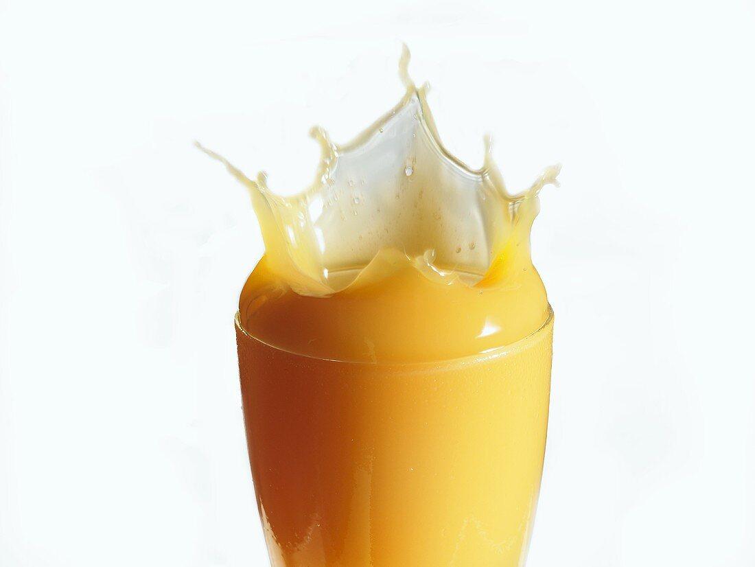 Mango nectar splashing out of a glass