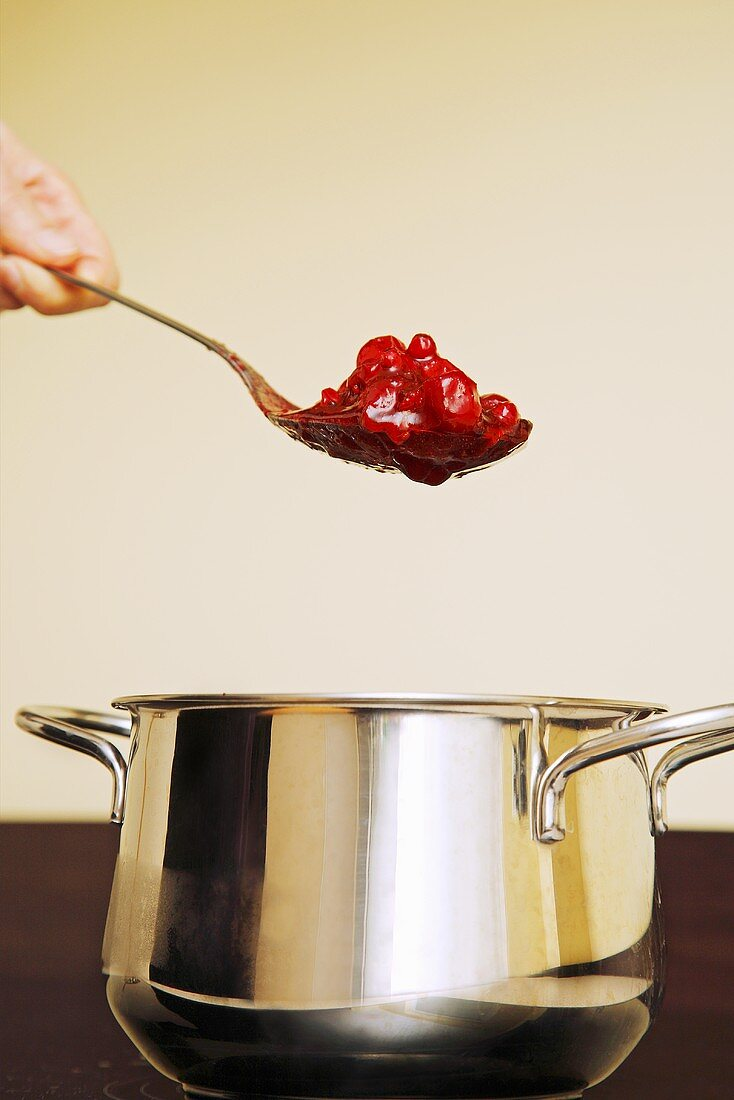 Hand holding a spoonful of red berry compote over a pan