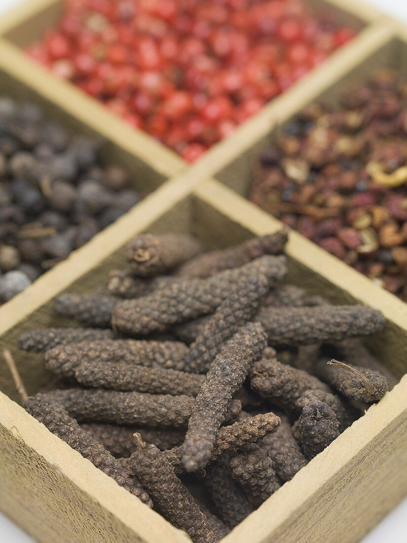 Spices and dried berries in wooden container
