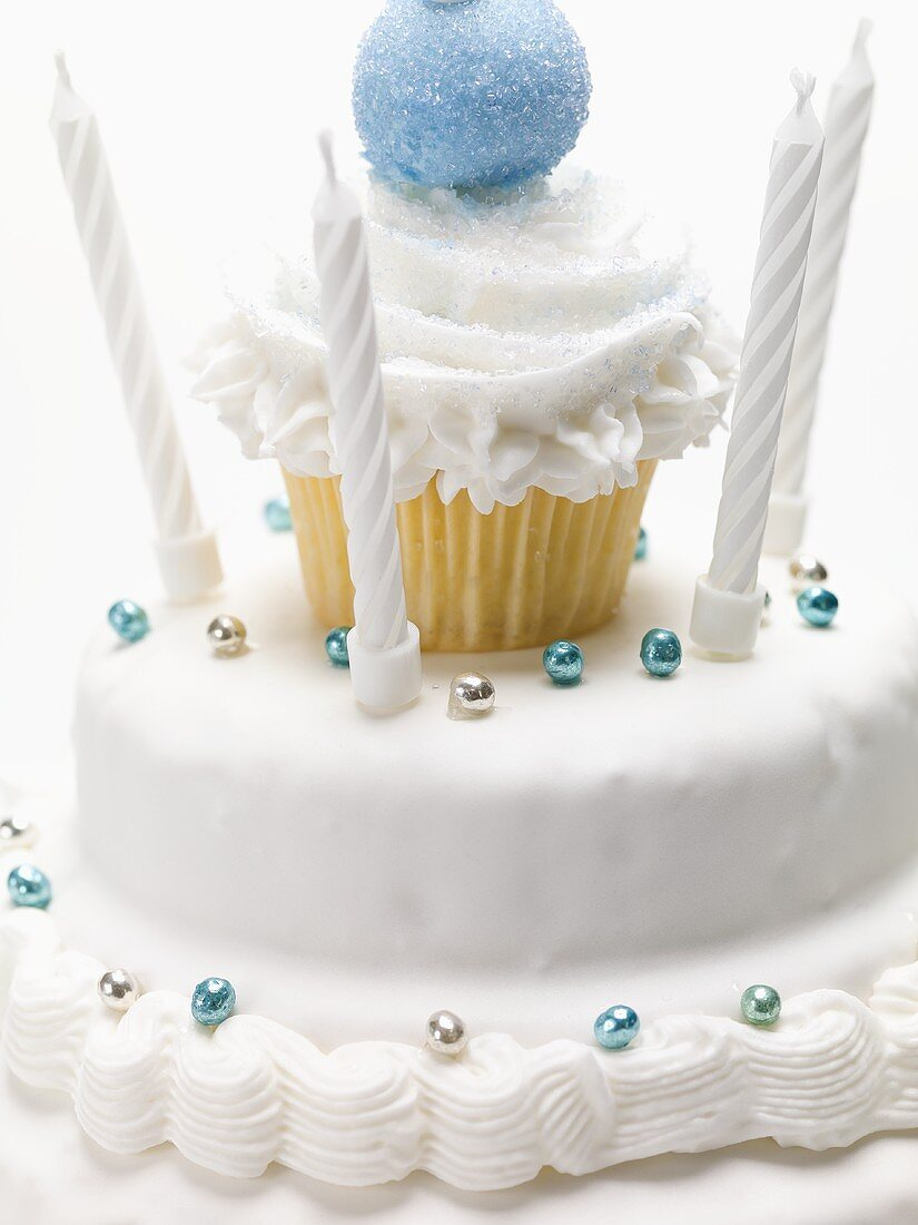 White birthday cake with dragées and candles