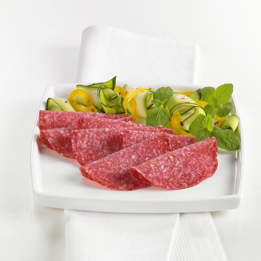 Slices of salami on plate with vegetable garnish