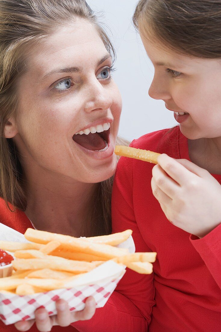 Young woman and girl eating chips together