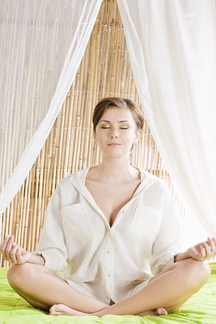 Young woman sitting cross-legged (practising yoga)