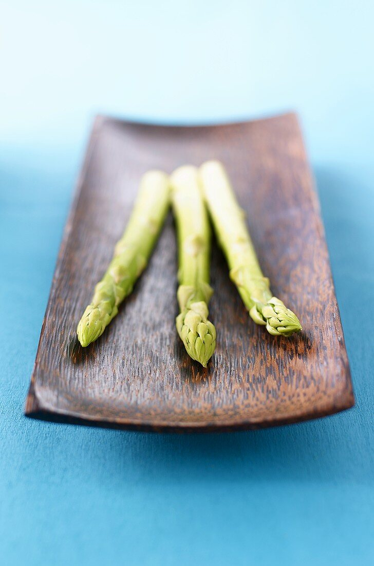 Three spears of green asparagus in wooden dish