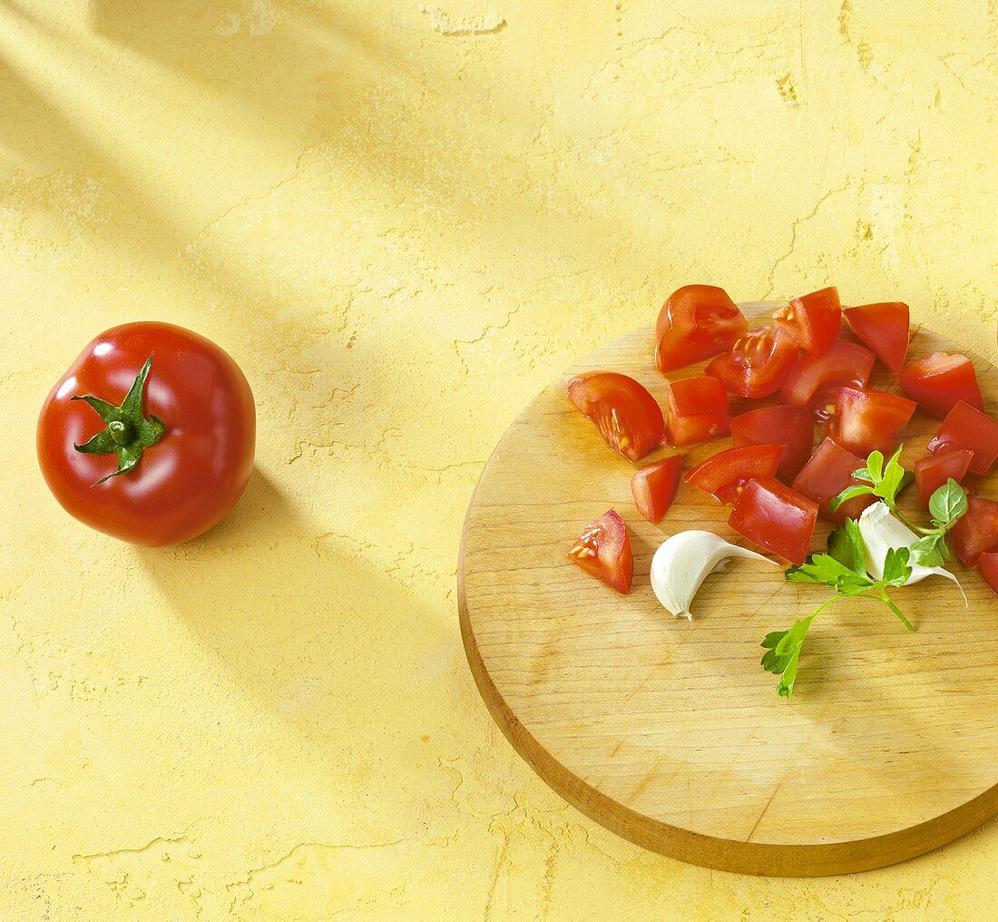Diced tomatoes, garlic & parsley on chopping board, whole tomato
