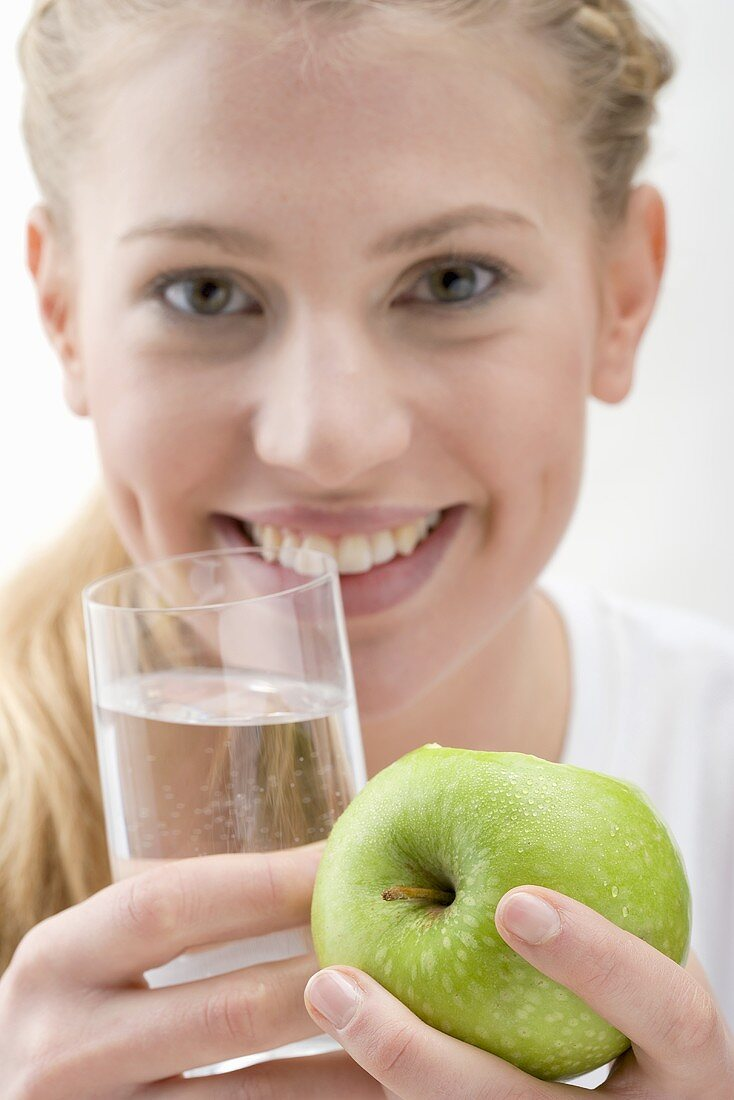 Woman holding apple and glass of water