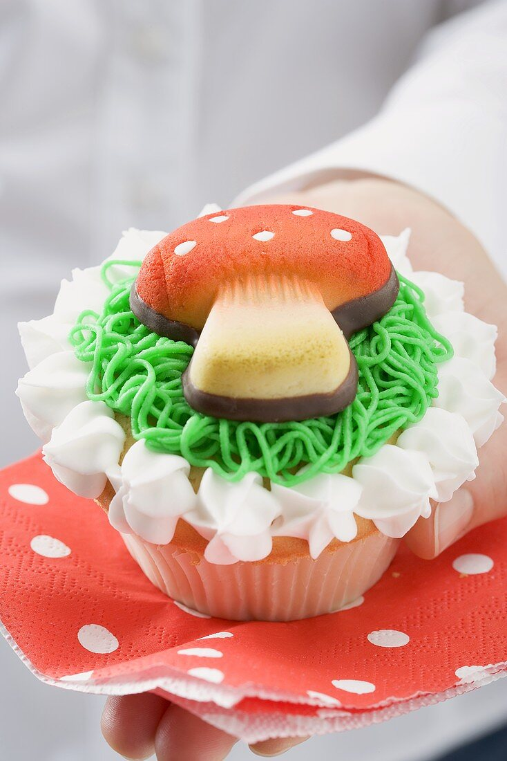 Hands holding cupcake with marzipan fly agaric