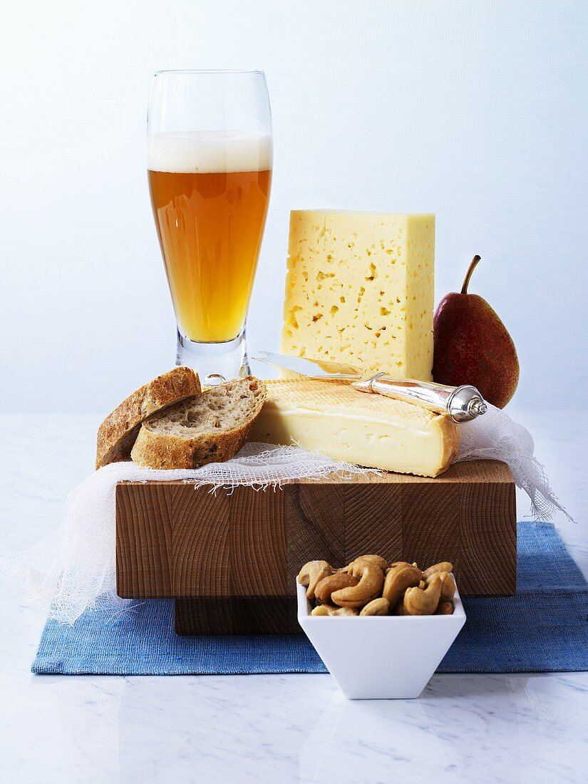 Cheese, bread, pear and wheat beer on a board