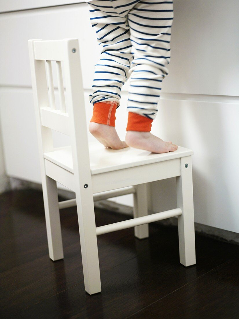 Small child standing on a white chair