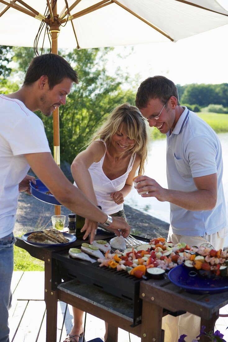 One woman and two men barbecuing food