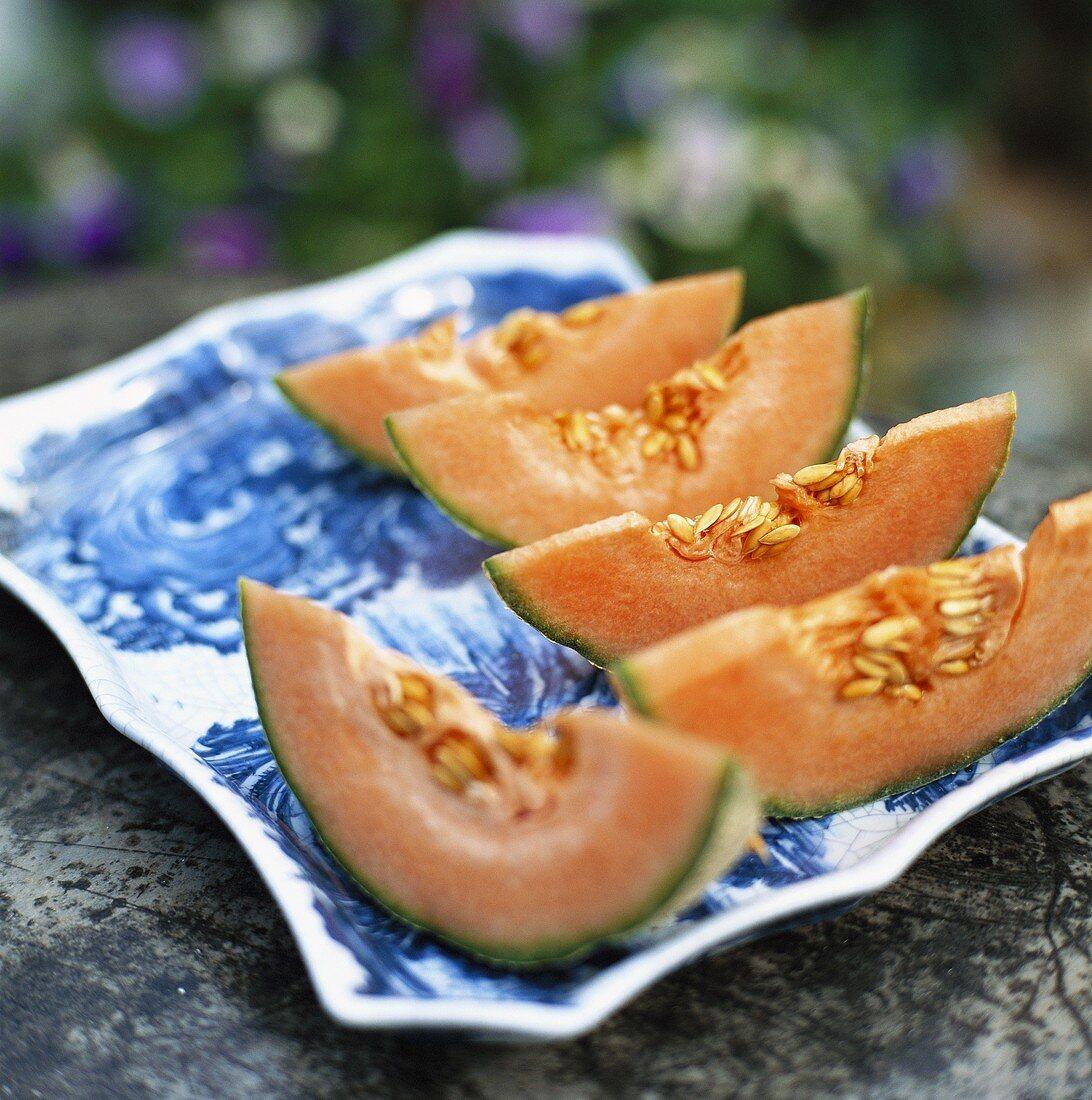 Slices of cantaloupe melon on porcelain plate