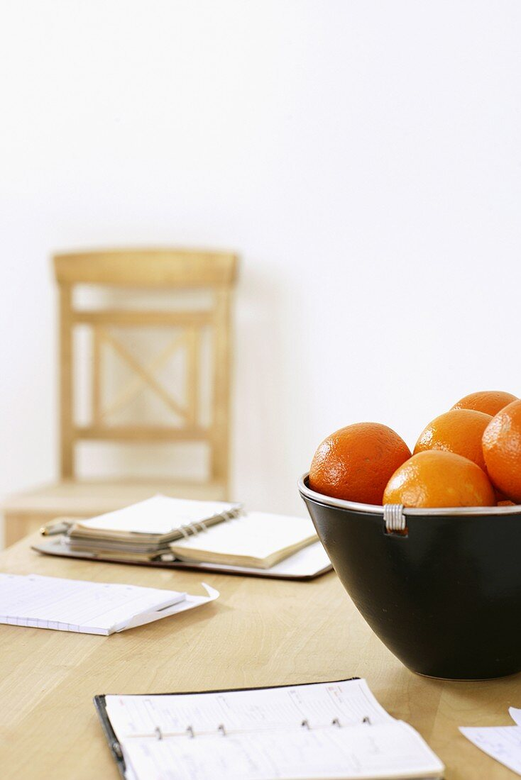 Two planners and oranges on an office desk