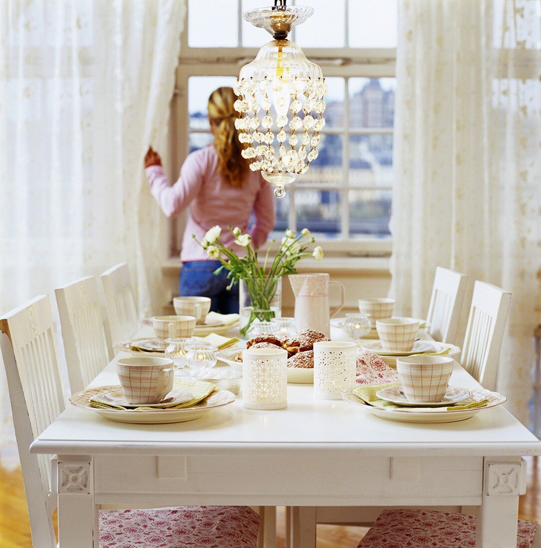 Table laid in white, woman at window in background