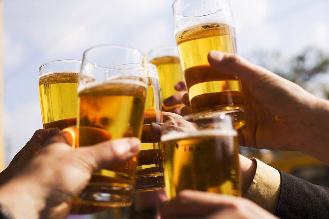 Hands raising glasses of beer
