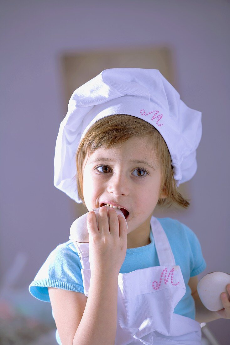 Little girl in chef's hat eating gingerbread