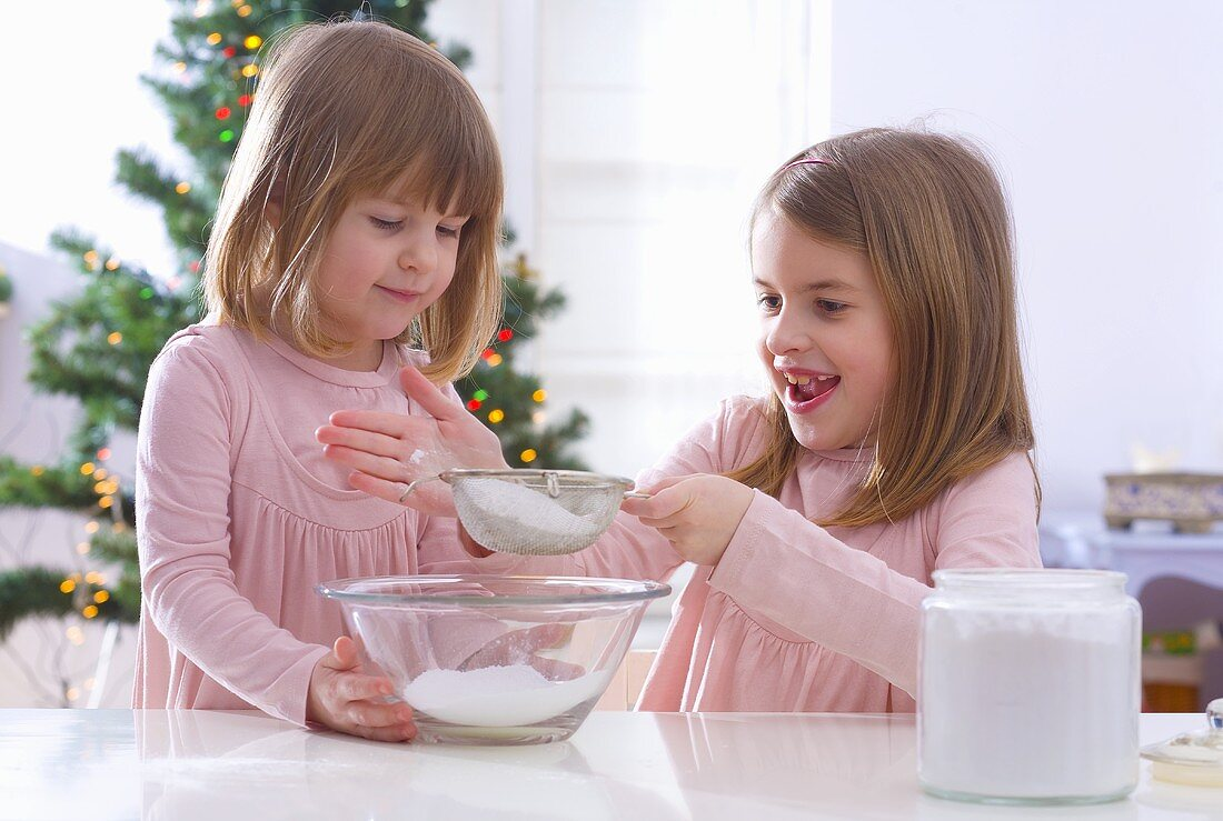 Christmas baking: two girls sieving icing sugar