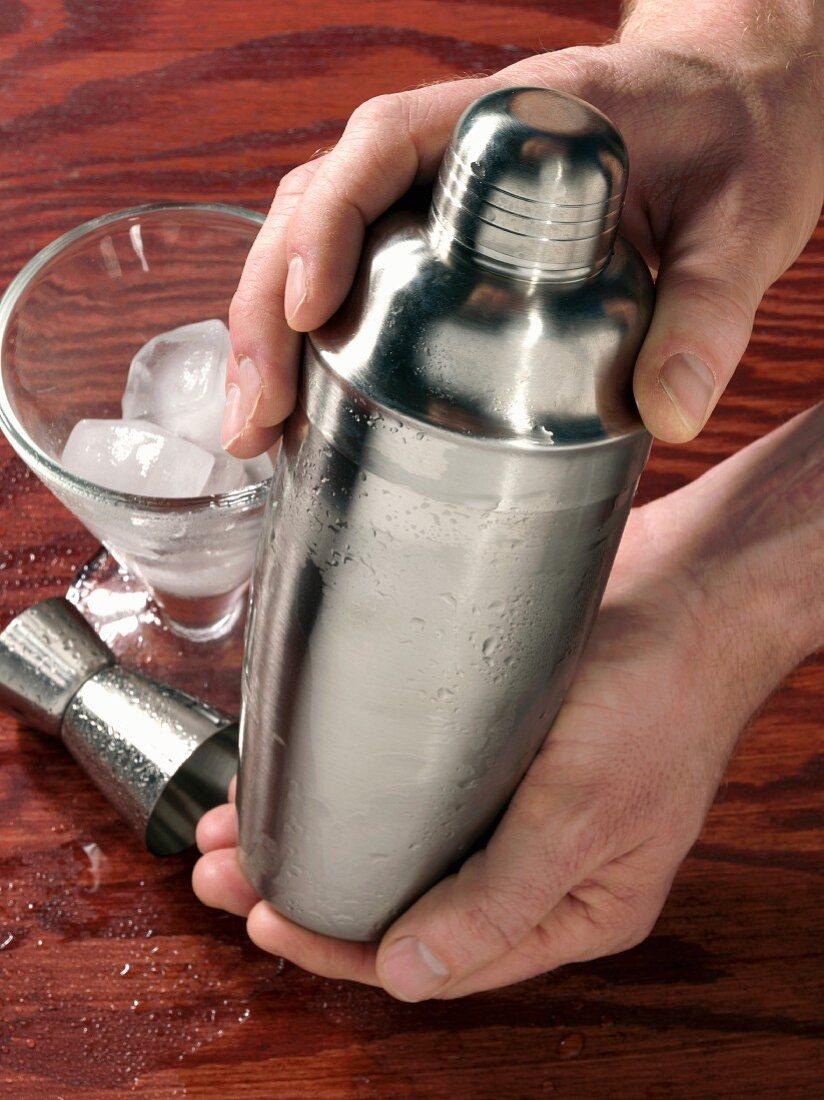 Hands holding cocktail shaker