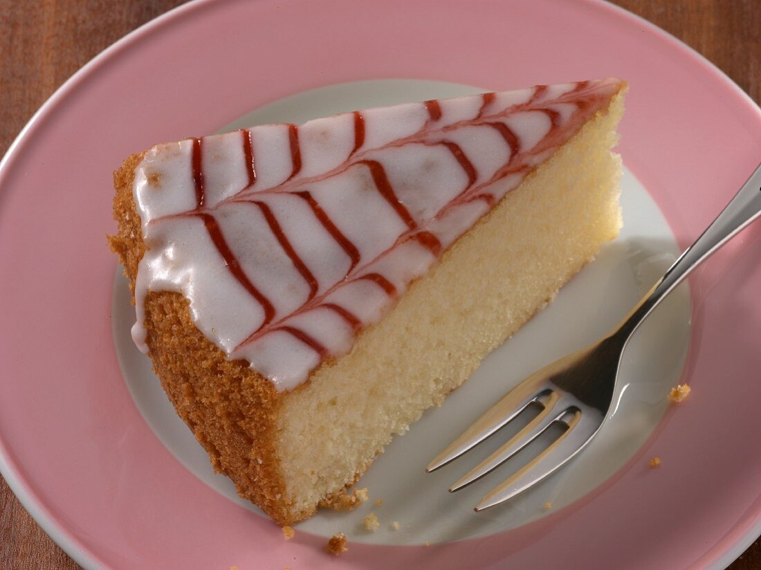 A slice of cake with icing and redcurrant jam