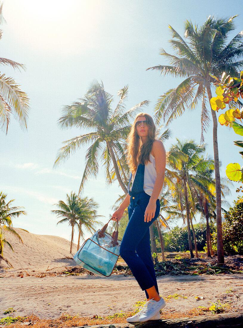 Brünette Frau geht in blauem Neck- holder - Overall zum Strand