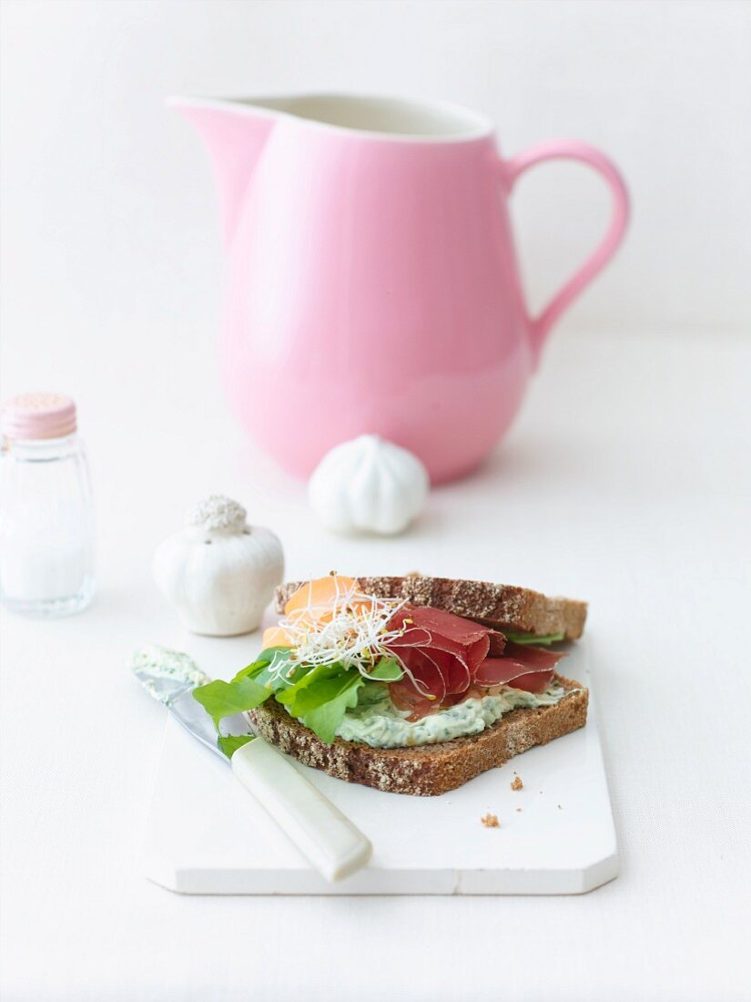 A sandwich with pesto cream cheese, bean sprouts and ham