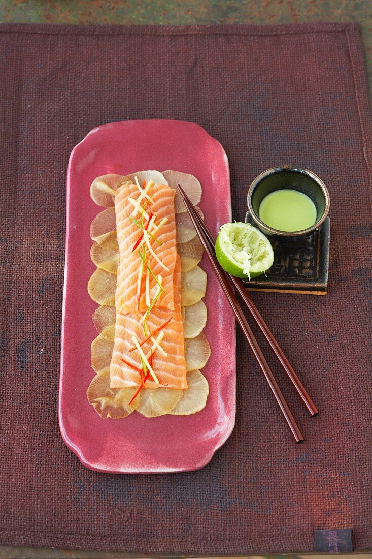 Raw salmon on a bed of radishes with wasabi sauce