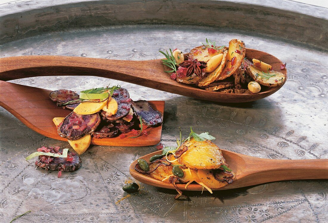 Three types of spicy potatoes on wooden spoons