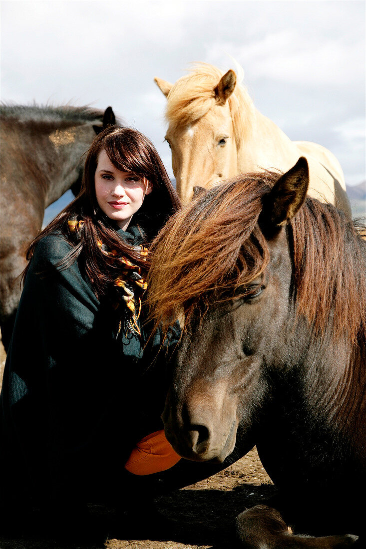 Beautiful brown haired woman wearing poncho and scarf crouching next to iceland horses