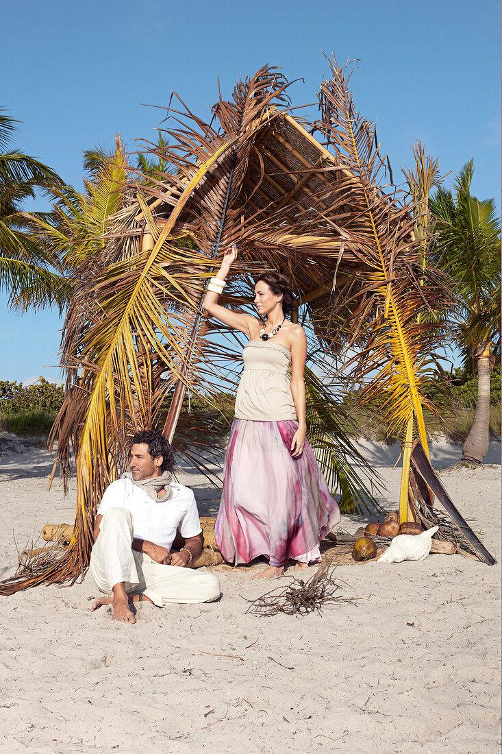 Paar am Strand, blicken zur Seite, Palmenhütte, Mann sitzt, Frau steht